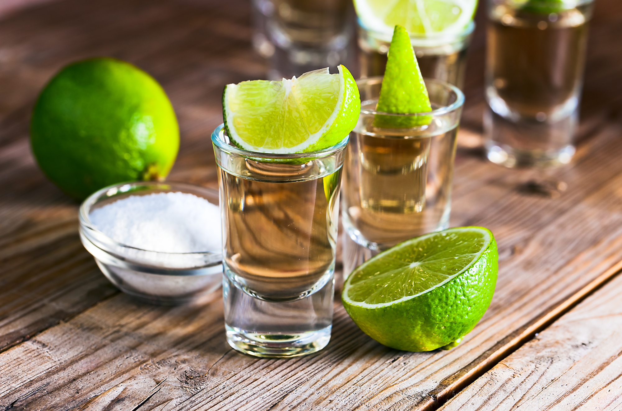 tequila shots on a table with limes