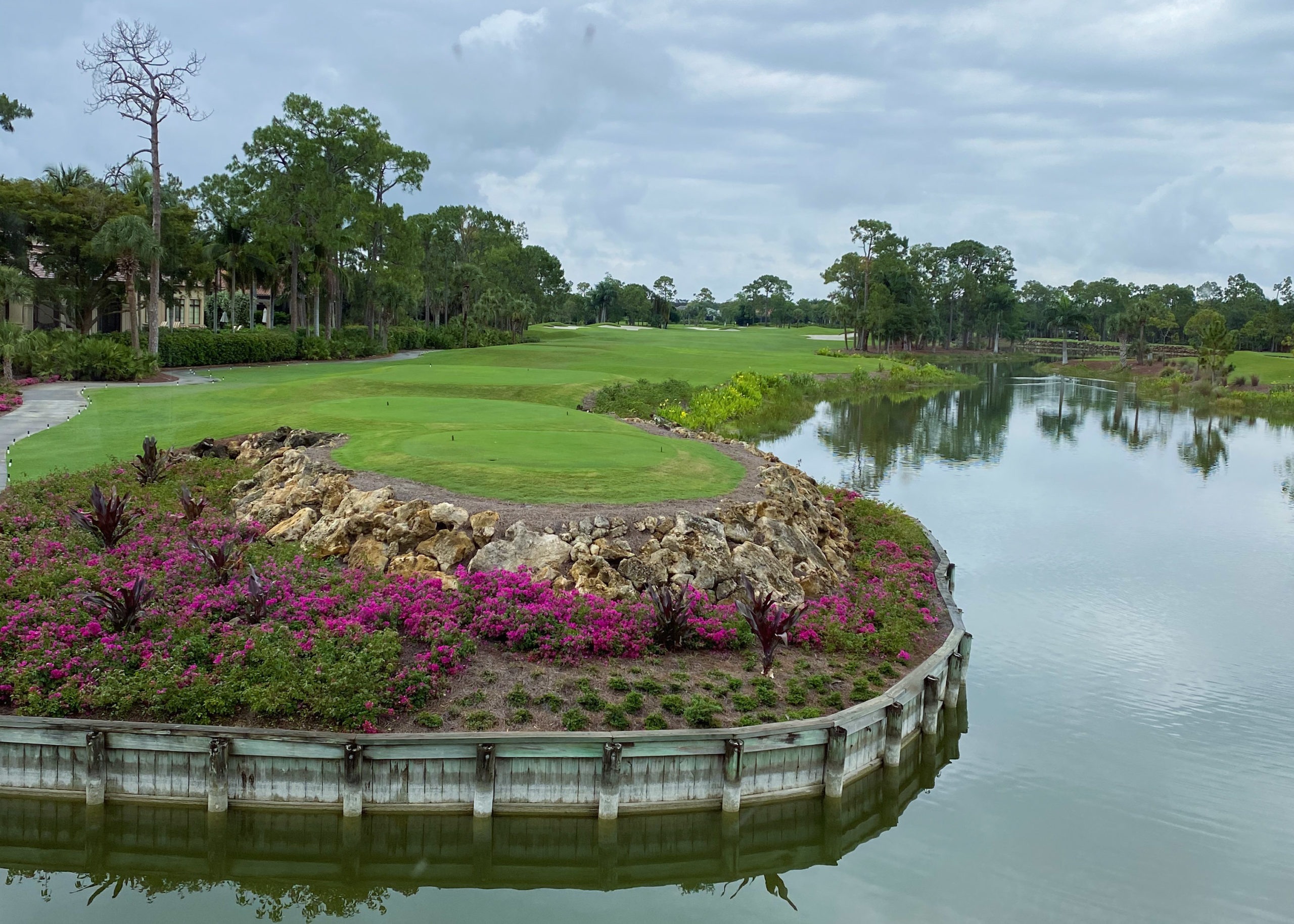 view of a golf course, water and flowers